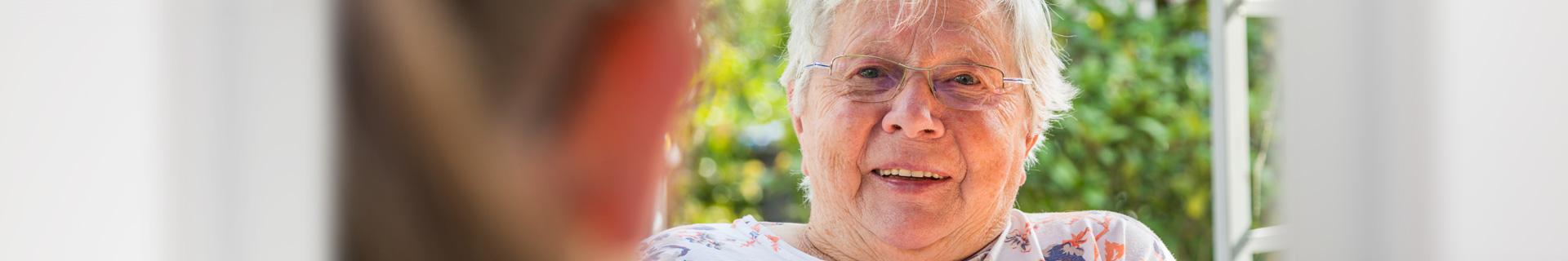 Ältere zu pflegende Dame unterhält sich im Garten