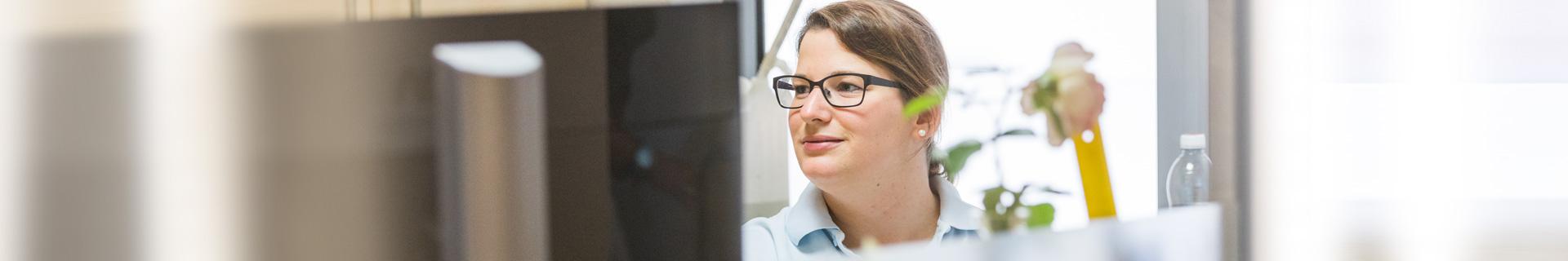 Eine Mitarbeiterin arbeitet am Schreibtisch